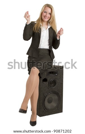A beautiful blonde businesswoman snapping her fingers to the rythm of the music coming from the speaker on which she is sitting.