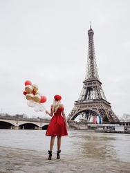A beautiful blonde girl in a red dress and with red balloons stands with her back on the seine embankment overlooking the Eiffel Tower in Paris.