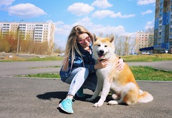 a beautiful blonde girl walks around the city in the summer with her dog Akita inu