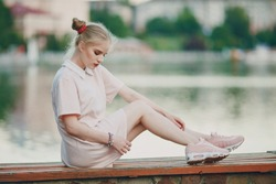 A beautiful blonde in a pink dress sittink near lake