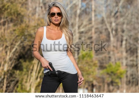 Stock Photo A beautiful blonde model holds a pistol for protection on a sunny day.