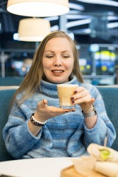 A beautiful blonde woman enjoys a fragrant latte in a cafe in the evening.