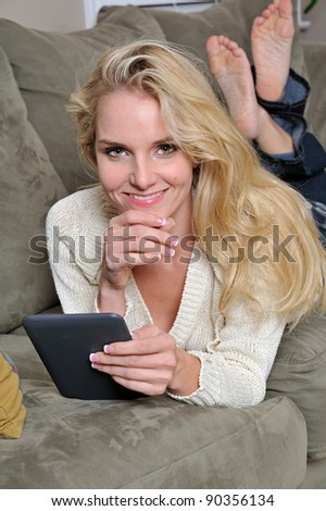 A beautiful blonde woman in a sweater relaxes on a couch using her e-reader or tablet - smiling with bare feet in the background