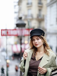 A beautiful blue-eyed blonde in a cap and trench coat stands on a Parisian street near the metro exit in Montmartre. Stylish Parisian woman on the street