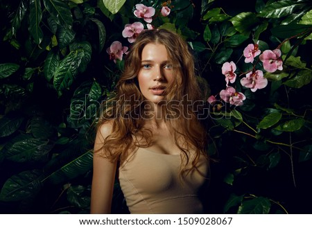 A beautiful blue-eyed long-haired brown-haired woman stands on a background of exotic plants and pink orchids.Beauty, fashion, cosmetology, natural, nature, natural, spa, detox, plants.