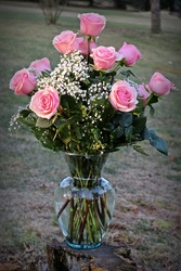 A beautiful bouquet of a dozen blooming gorgeous roses outside with a sunny background.