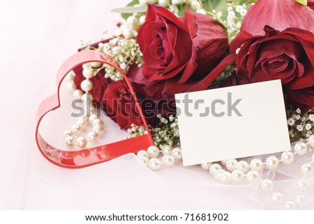 A beautiful bouquet of red roses with red heart, pearls, and gift tag with copy space on pink tulle background