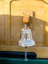 A beautiful brass bell is hanging on the decks of an antique tall ship on Lake Michigan USA