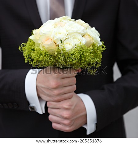 A beautiful bridal bouquet at a wedding party in the hand of the groom
