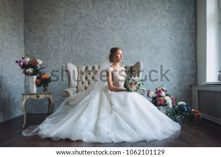 A beautiful bride is sitting in the studio on the couch in a lace dress. Sweet bride in a gray studio. Portrait of the bride.