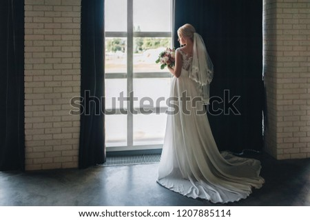 A beautiful bride is standing near a window in a gray studio with a gorgeous bouquet. Wedding portrait. Wedding interior. Wedding photography. #1207885114