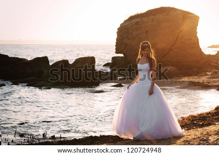 A beautiful bride walking across the cliff on the sea