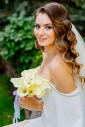 A beautiful bride with long curls in a long dress sits on a park bench among grass and trees. wedding photo shoot.