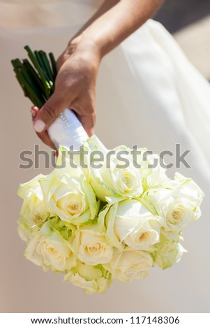 A beautiful bride with white roses in the hand.