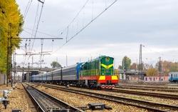 A beautiful, bright, freshly painted diesel locomotive ChME3 with blue passenger cars arrives at the Kharkiv railway station. Autumn shot. Ukrainian railways.