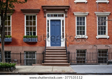 a beautiful brownstone townhouse with a blue door in a famous neighborhood in Manhattan, New York City.