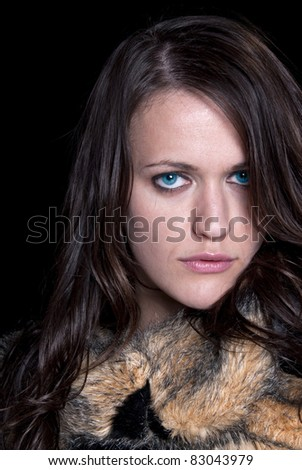 A beautiful brunette model wearing a fur coat - stock photo