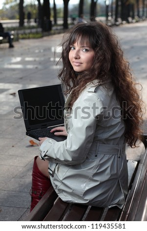 A beautiful brunette model working on a computer.