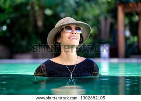 53514bc0f A beautiful brunette woman wearing black lace bikini pairing with straw hat  and sunglasses poses inside