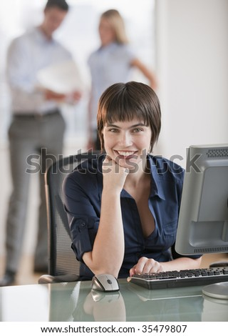 A beautiful brunette working at a computer, while two employees discuss paperwork behind her.  She is smiling. Vertically framed shot.