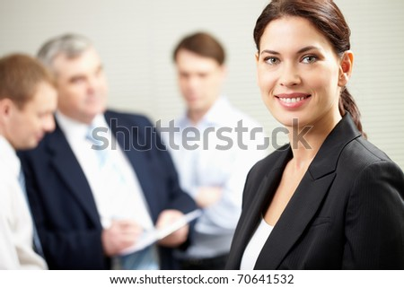 A beautiful businesswoman against her colleagues