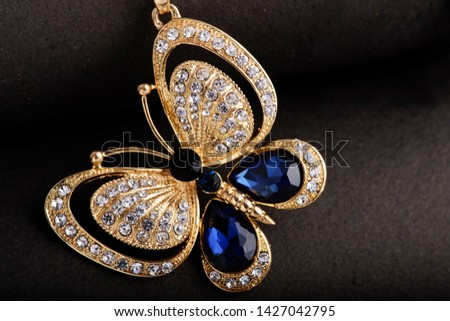 A beautiful butterfly pendant. This is a pure western wear. Best suitable for evening wears. The diamonds and the blue stones give a nice contrast with the golden base. #1427042795