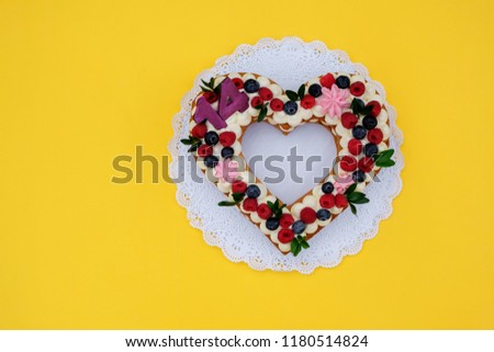 a beautiful cake in the shape of a heart with the number fourteen on a yellow background #1180514824