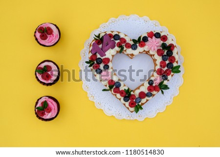 a beautiful cake in the shape of a heart with the number fourteen on a yellow background #1180514830