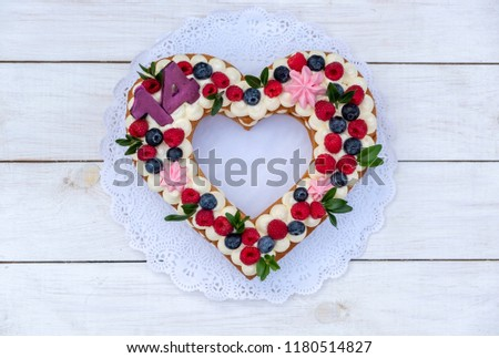 a beautiful cake in the shape of a heart with the number fourteen on white background #1180514827