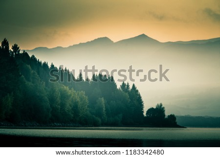 A beautiful, calm morning landscape of lake and mountains in the distance. Colorful summer scenery with mountain lake in dawn. Tatra mountains in Slovakia, Europe.