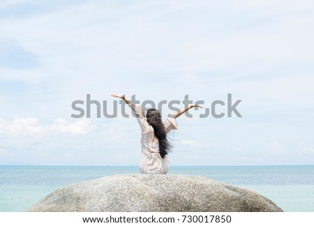 A beautiful carefree woman on travel vacation sitting on an idyllic tropical sea beach rock and stretching arms. New beginnings, well being, freedom, dreamlike and escapism concepts. #730017850