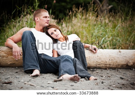 A beautiful caucasian couple in love sitting on the beach
