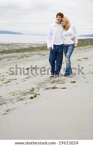 A beautiful caucasian couple in love walking on the beach