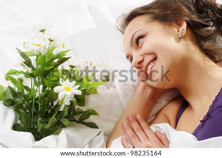 A beautiful caucasian fortune girl in bed with a bouquet of flowers on a light background