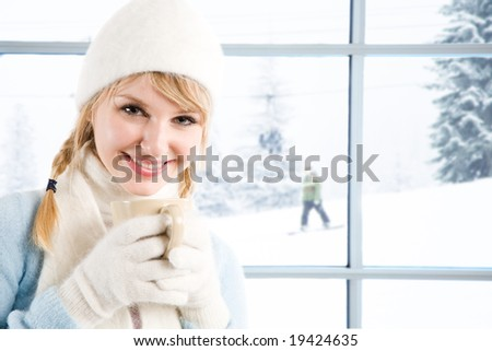 A beautiful caucasian girl drinking hot coffee at a ski resort