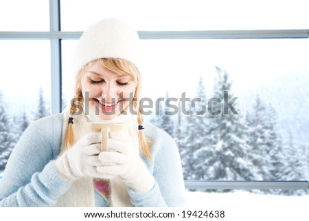 A beautiful caucasian girl drinking hot coffee at a ski resort on a snowy day