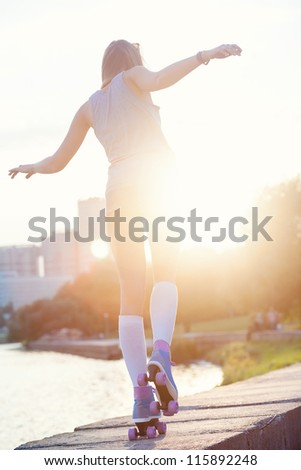 A beautiful caucasian roller skater woman during the sunset, outdoor
