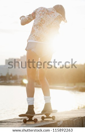 A beautiful caucasian skater woman during the sunset, outdoor