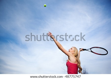 A beautiful caucasian tennis player serving the ball on the tennis court