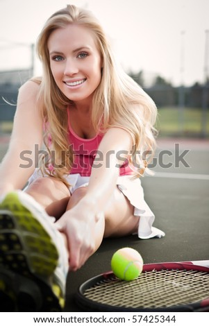 A beautiful caucasian tennis player stretching on the tennis court