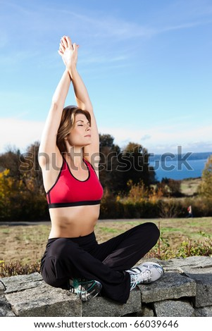 A beautiful caucasian woman doing yoga meditation outdoor in a park