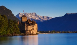 A beautiful chateau by a lake with the mountains in the back