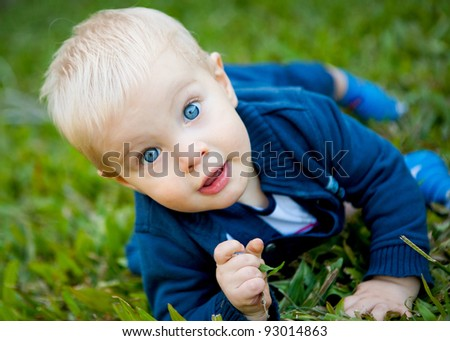A beautiful cheeky baby boy on the grass making eye contact with the camera