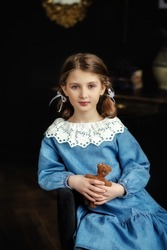 A beautiful child girl with two pigtails in a blue dress with a white lace collar is holding a retro teddy bear in her hands. Retro style. Denim dress. Fabulous photo. Selective focus of the image