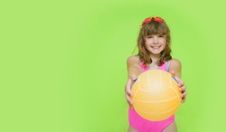 A beautiful child in a pink swimsuit shows a beach volleyball ball to the camera. Plortret of a cute little girl with swimming goggles on a green background. The concept of summer holidays.