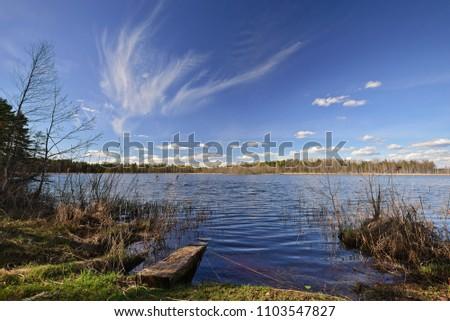 A beautiful cirrus cloud over the forest lake. Nature landscape. Novgorod region, Russia.