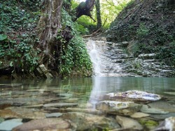 A beautiful clean waterfall in layered rocks flows into the baptismal font in a fast stream. Aquamarine font at the foot of the waterfall. Stones in the water, around the forest. Mountain landscape