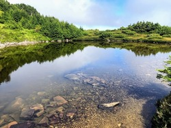 A beautiful clear lake with the clouds reflecting in the water, on mount raymond, along the sleeping beauty trail in haida gwaii, british columbia, canada