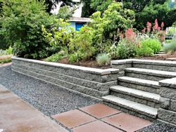 A beautiful closeup view of a staircase incorporated into a block retaining wall with steps leading into existing landscaped garden
