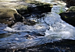 A beautiful closeup view of water rushing over bedrock ledges of riverbed